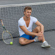 Tennis player sitting besides the net — Stock Photo