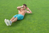 Young man doing sit-ups on green grass — Stock Photo