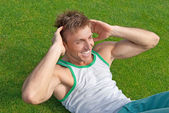 Outdoor training. Young man doing sit-ups. — Stock Photo