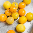 Washing yellow tomatoes and lemons — Stock Photo
