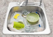 Dishes soaking in the kitchen sink — Stock Photo
