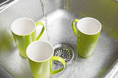 Washing green cups in the kitchen sink — Stock Photo