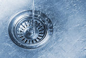Water running into kitchen sink drain — Stock Photo