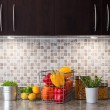 Vegetables, fruits and herbs in a kitchen with cozy lighting - Lizenzfreies Foto