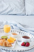 Tray with tasty breakfast on a bed — Stock Photo