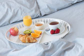 Tray with healthy breakfast on a bed — Stock Photo