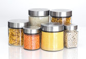 Food ingredients in glass jars, on white background — Stock Photo