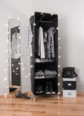 Clothes organizer and mirror decorated with lights — Stock Photo