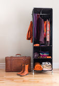 Mobile wardrobe with clothing and leather suitcase — Stock Photo