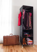 Leather suitcase and mobile wardrobe with clothing — Stock Photo
