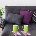 sofá con cojines brillantes y tazas verdes sobre una mesa — Foto de Stock