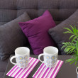 Sofa with cushions and two cups on a table — Stock Photo
