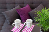 Sofa mit kissen und zwei tassen auf dem tisch — Stockfoto