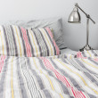 Metal lamp near bed with colorful bedclothes — Stock Photo