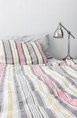 Renkli yatak örtüsü yatak yakınındaki metal lamba — Stok fotoğraf