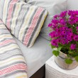 Stock Photo: Bright purple flowers decorating bedroom