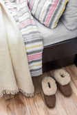 Cozy slippers near bed — Stock Photo