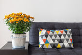 Orange chrysanthemums and bright cushion on a sofa — Stockfoto