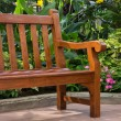Wooden bench in the tropical garden — Stock Photo