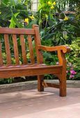 Wooden bench in the tropical garden — Stock Photo