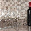 Stock Photo: Bottle of wine and glasses on kitchen countertop