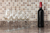 Bottle of wine and glasses on kitchen countertop — Stock Photo