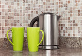 Electric kettle and cups in the kitchen — Stock Photo