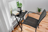 Chair and table in a room with green plants — ストック写真