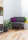 Corner of a living room with gray armchair and plants — Stock Photo