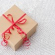 Present with red ribbon on a knitted background — Stock Photo