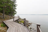 Rocky lakeshore with wooden pathway — Stock Photo