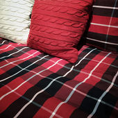Checked bed clothing and cushions — Stock Photo