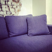 Blue textile sofa near brick wall — Stock Photo