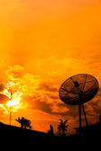 Reception antenna and satellite dish with orange sky — Stok fotoğraf
