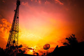 Reception antenna and satellite dish with  orange sky — Stock Photo