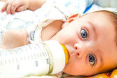 Baby and milk bottle — Stock Photo