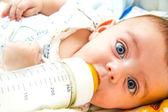 Baby and milk bottle — Stock Photo