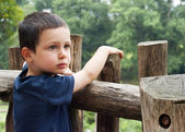 Child by fence — Stock Photo