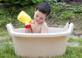 Child playing in water backet — Stock Photo