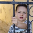 Child behind a gate or fence — Stock Photo