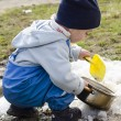 Child playing with snow in spring — Stock Photo #35873113