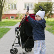 Child pushing stroller — 图库照片