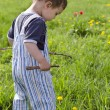 Child playing on grass with sticks of wood. — Stock Photo