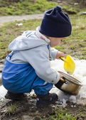 Child playing with snow in spring — Stock Photo