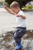Child jumping in puddle — Stock Photo