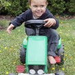 Child driving toy tractor — Stock Photo