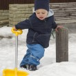 Winter child with snow shovel — Stok fotoğraf
