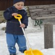 Winter child with snow shovel — Stockfoto