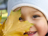 Child with autumn leaf — Stockfoto