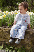 Child in spring flower garden. — Stock Photo
